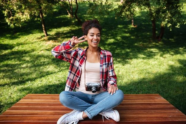 公園の屋外に座っている女性写真家。