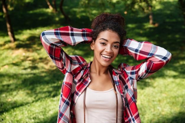 公園の屋外に座っている素晴らしい若いアフリカ人女性