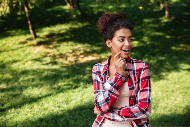 公園の屋外に座っているかなり若いアフリカ人女性。