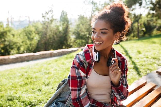屋外の公園で座っている幸せな若いアフリカ人女性。