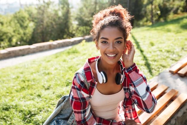 公園の屋外に座っているアフリカの女性。