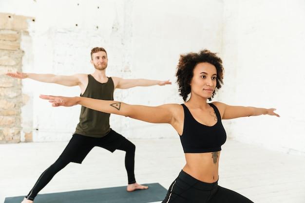 Молодой африканец и рыжий мужчина делают упражнения в тренажерном зале
