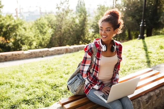 ラップトップコンピューターを使用して公園の屋外に座っているアフリカの女性。