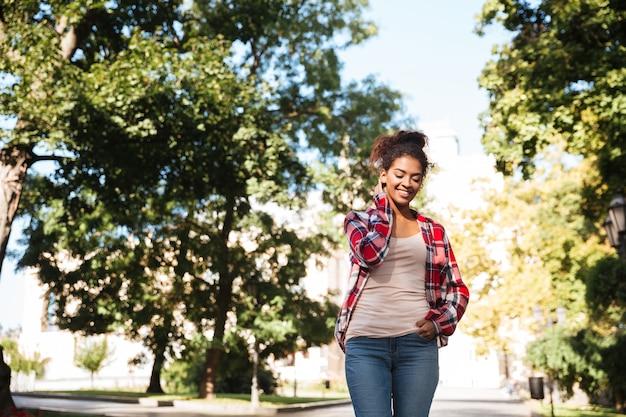 公園で野外を歩いているアフリカの女性