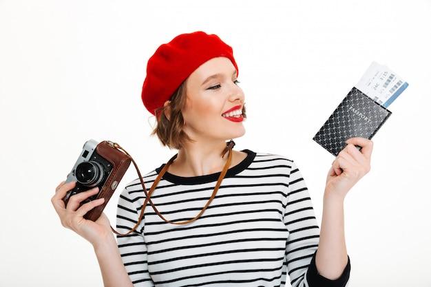 チケットとパスポートを保持しているカメラで若い観光客女性