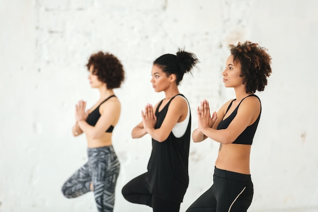 Группа молодых женщин, делающих упражнения йоги