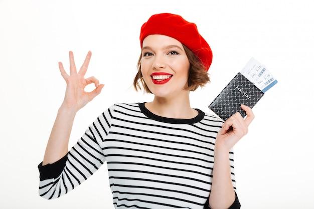 チケットとパスポートを保持している若い幸せなツーリストの女性