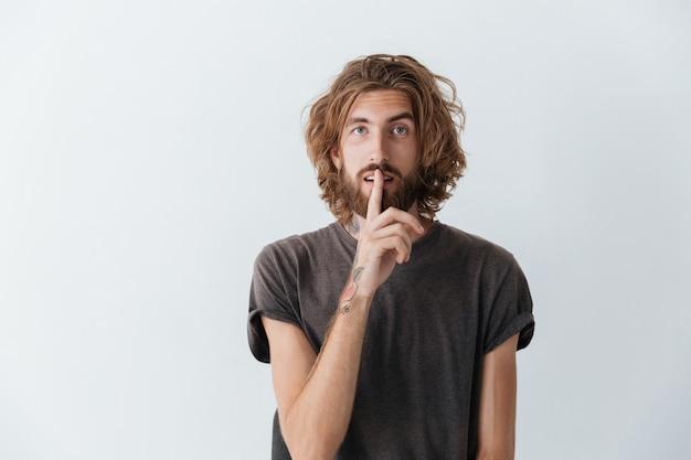 白人のひげを生やした青年が沈黙のジェスチャーを作る。