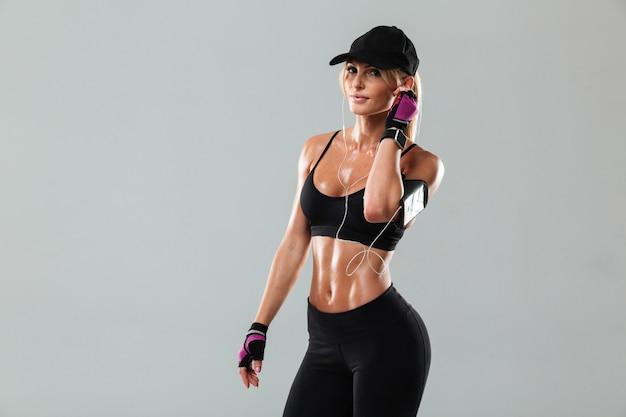 Великолепная молодая спортивная леди, стоящая слушает музыку