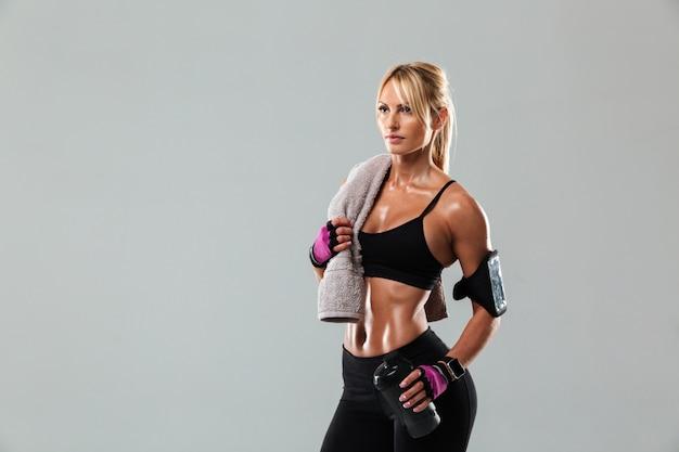 Молодая белокурая спортсменка держа полотенце и бутылку с водой стоя