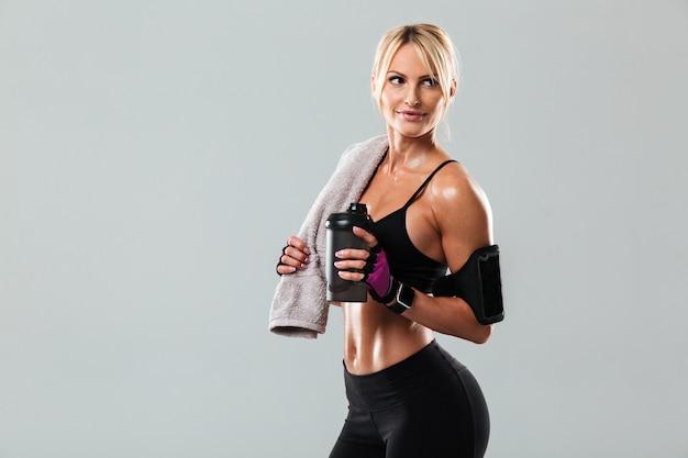 Улыбающаяся блондинка спортсменка держит полотенце