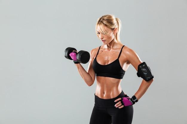 Молодая сконцентрированная женщина спортсмена делая тренировки с гантелью