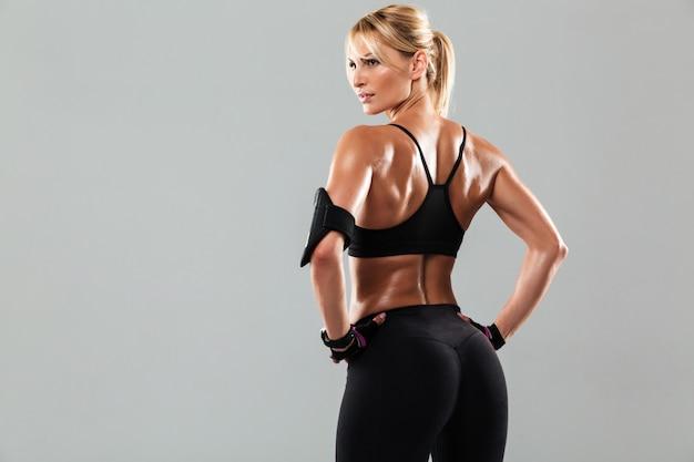 立っている健康的な筋肉のスポーツウーマンの背面図の肖像画