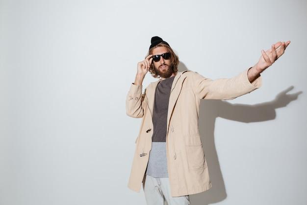 孤立した立っているサングラスを身に着けているひげを生やした流行に敏感な男