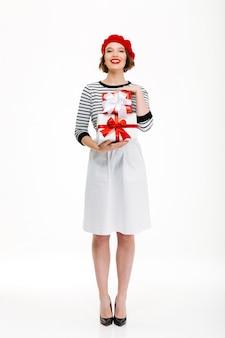 Молодая жизнерадостная женщина держа коробку сюрприза подарка.