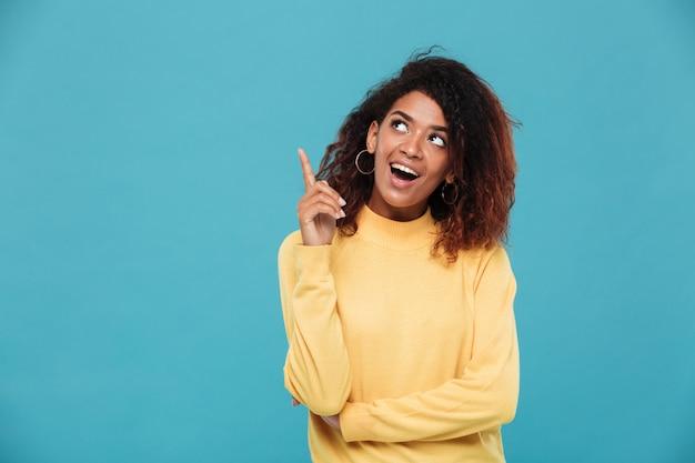 暖かいセーターに身を包んだ陽気な若いアフリカ人女性