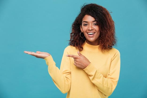 指している暖かいセーターに身を包んだ幸せな若いアフリカ女性。