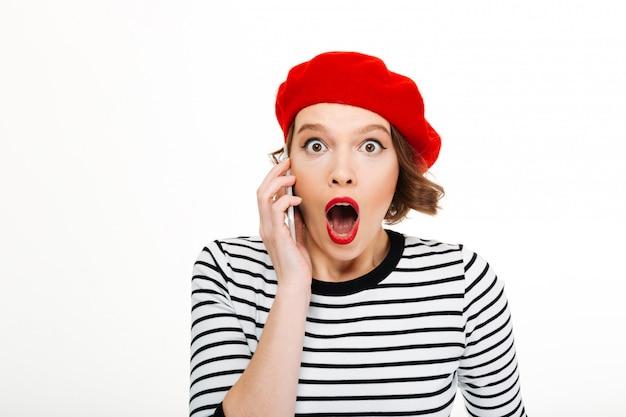 携帯電話で話している若いショックを受けた女性