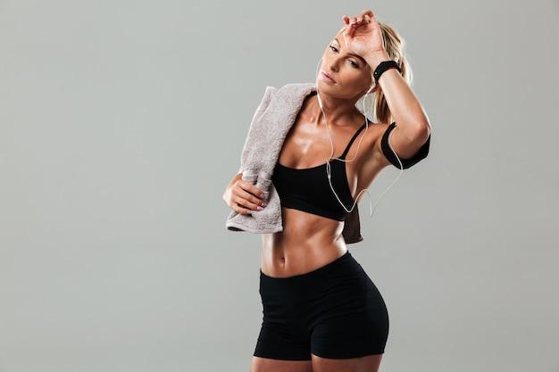 Усталая молодая спортивная леди, стоящая слушает музыку