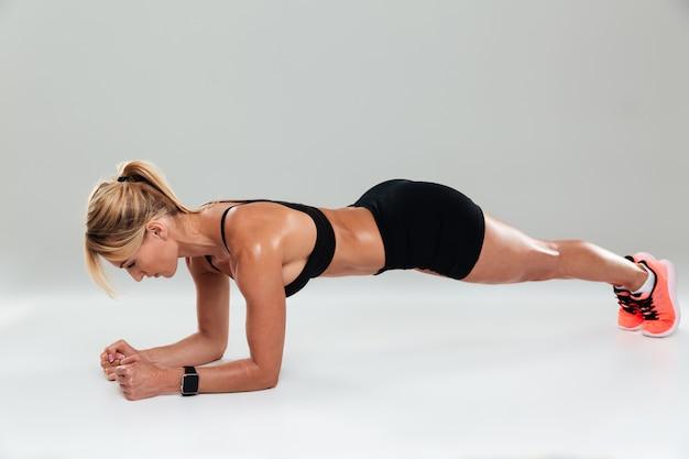 板のエクササイズをしている集中した筋肉スポーツウーマンの全長