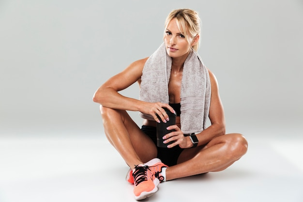 Красивая уставшая спортсменка с полотенцем на плечах