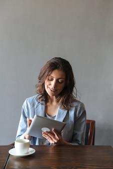 Усмехаясь женщина сидя внутри помещения используя планшет.