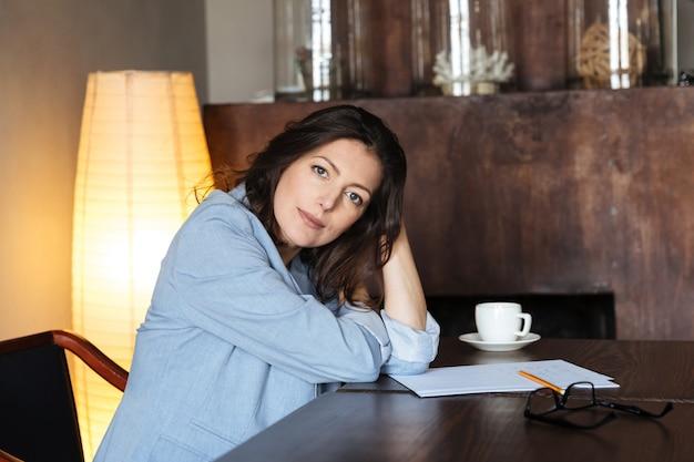 Улыбается женщина сидит в помещении возле чашки кофе
