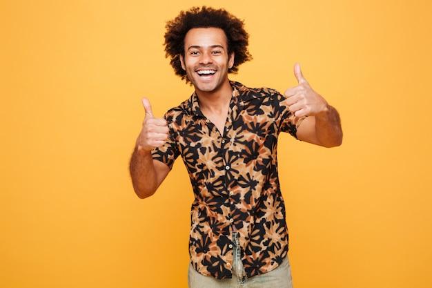 Веселый молодой африканский человек с большими пальцами руки вверх.