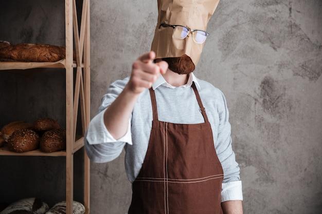 男のパン屋が指している頭に紙袋を立っています。
