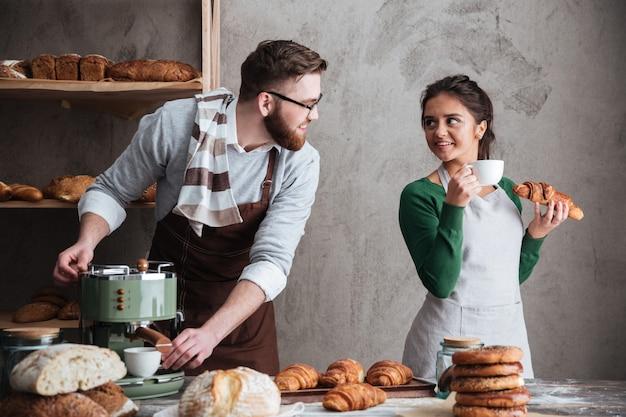 Веселая влюбленная пара пекарей пьют кофе