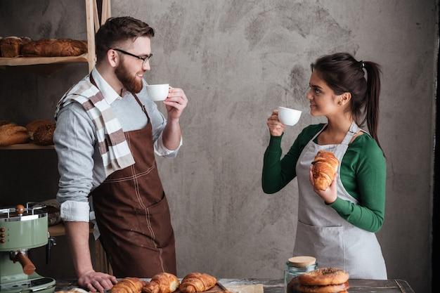Счастливая любящая пара пекарей пьет кофе