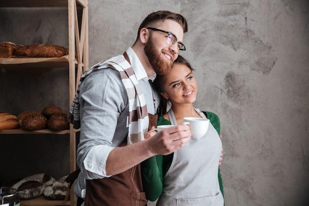 幸せな若い愛するカップルのパン屋がコーヒーを飲みます。