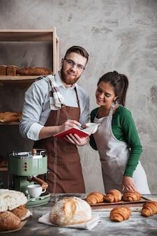 Счастливая любящая пара пекарей, стоя возле хлеба.