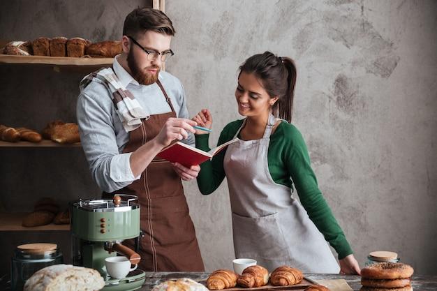 ノートブックを見て笑顔の愛情のあるカップルのパン屋。