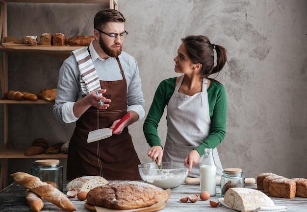 料理をしながら夫を聞く女性