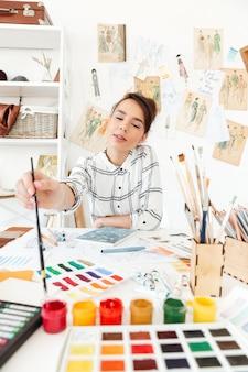 Молодая сосредоточенная женщина - иллюстратор моды