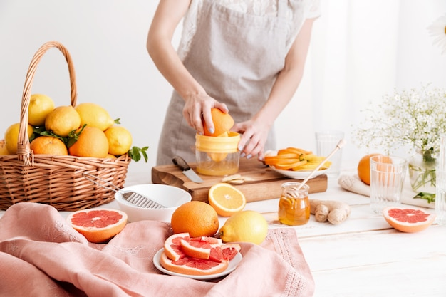 Обрезанное изображение женщины выжимает сок из цитрусовых.