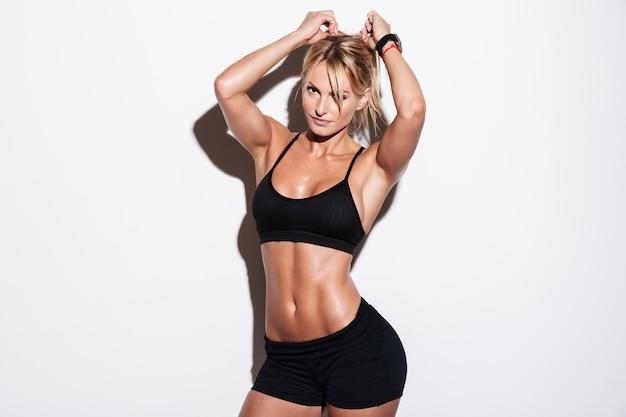 Довольно блондинка спортсменка позирует стоя