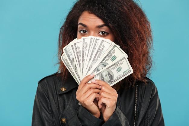 お金の後ろに隠れている革のジャケットの謎のアフリカの女性