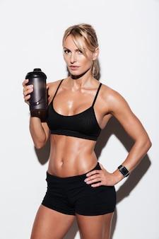 立っている間水のボトルを保持している若い健康なスポーツウーマン
