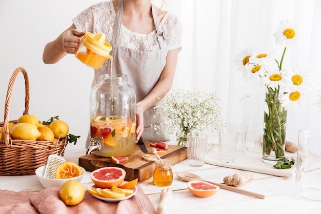 Удивительная сосредоточенная женщина, готовящая цитрусовый напиток.