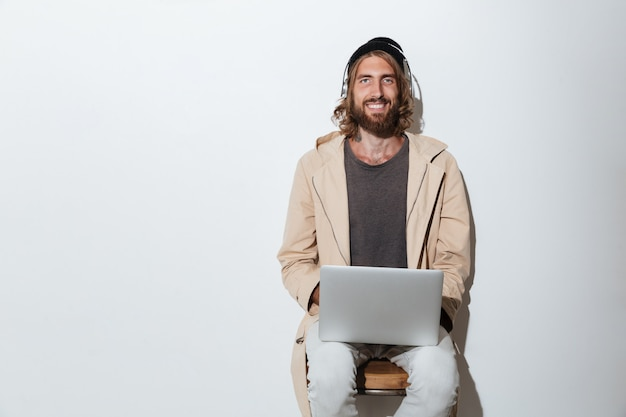 Счастливый человек битника смотря камеру используя портативный компьютер.