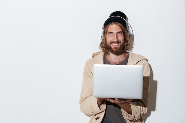 音楽を聴くラップトップコンピューターを使用して幸せな流行に敏感な男。