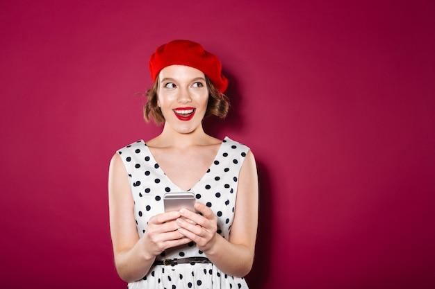 Хитрая улыбающаяся рыжая женщина в платье держит смартфон и смотрит в сторону розового