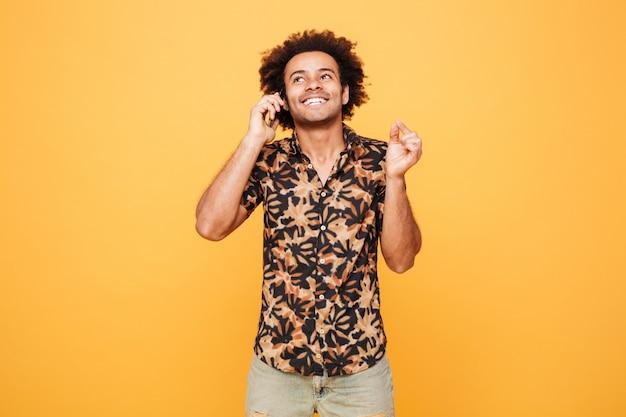 Счастливый молодой африканец разговаривает по телефону