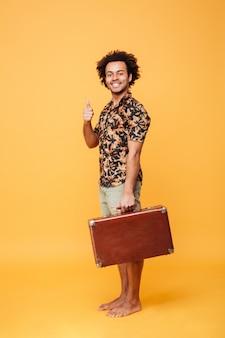 Счастливый молодой африканский человек держа чемодан показывая большие пальцы руки вверх.