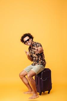 Полная длина портрет веселого молодого африканского туристического парня