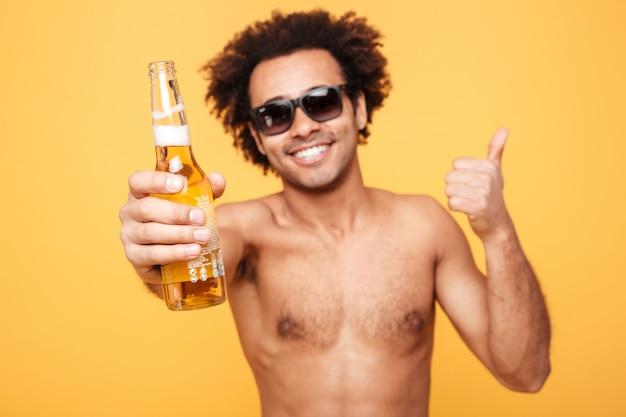 Жизнерадостный молодой африканский человек держа пиво показывая большие пальцы руки вверх