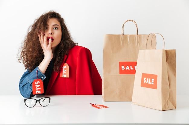 Взволнованная потрясенная распродажа женщина сидит с бумажными сумками