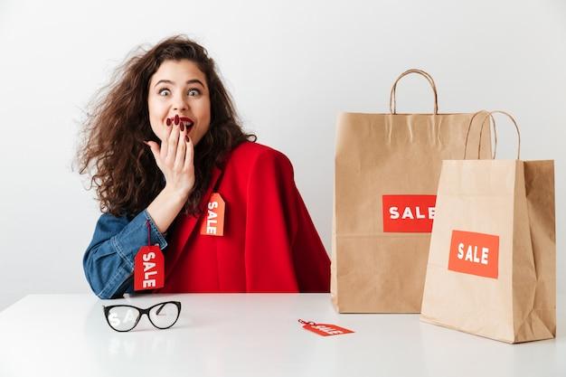紙の買い物袋で座っている興奮してうれしそうな女の子の買い物中毒